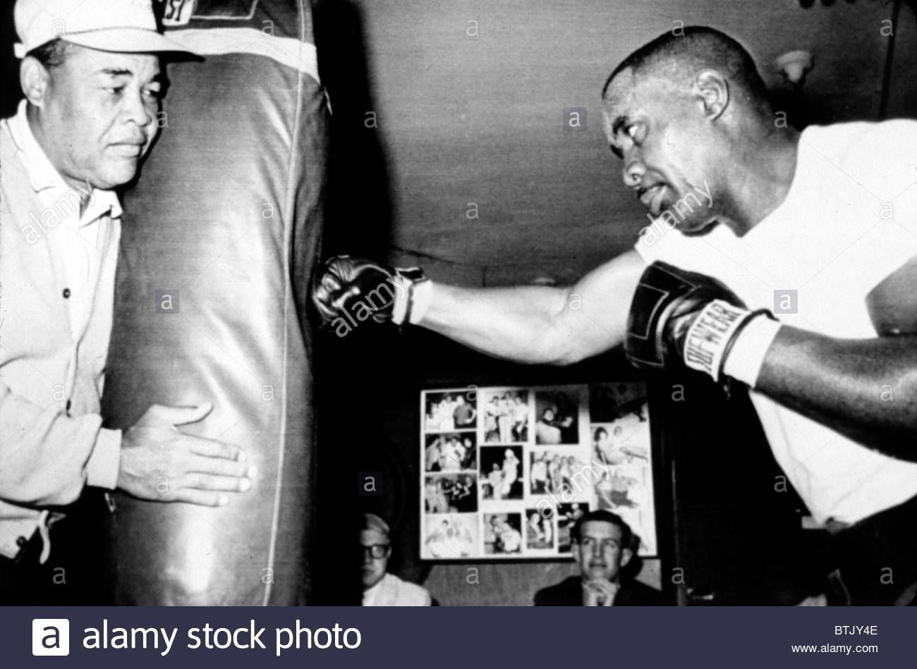 sonny-liston-working-out-on-the-heavy-bag-while-joe-louis-holds-it-BTJY4E.jpg