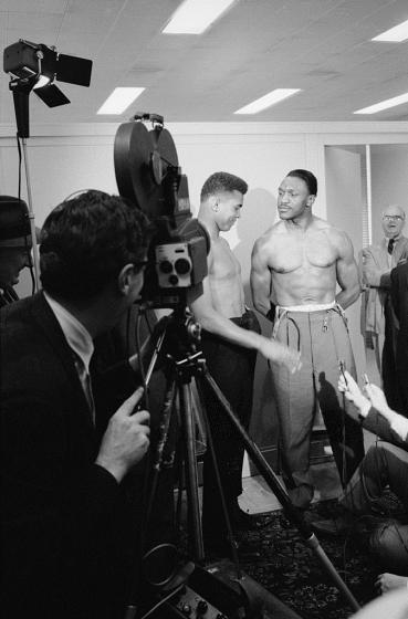 Ali_-_Cassius_Clay_smirks_at_fellow_boxer_Charlie_Powell_at_the_weigh-in_before_their_bout,_Pittsburgh,_Pennsylvania,_January_24,_1963