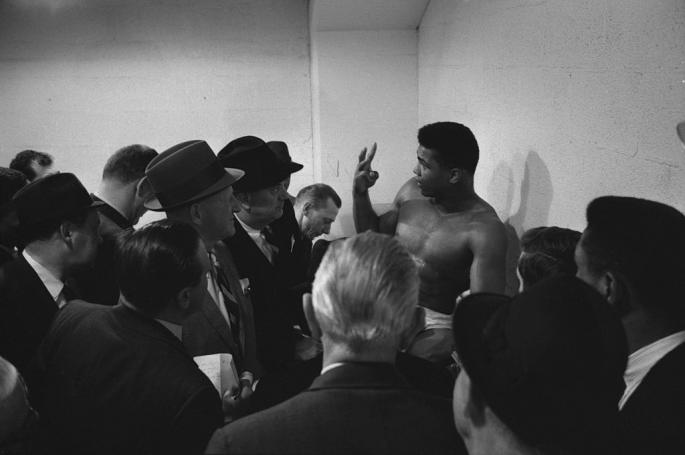 Cassius_Clay_(later_known_as_Muhammad_Ali,_1942_-_2016)_talks_with_the_press_before_a_bout_(against_Charlie_Powell)_at_Civic_Arena,_Pittsburgh,_Pennsylvania,_January_24,_19631
