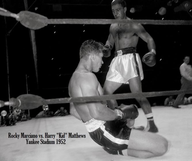 Harry_Matthews_sits_on_the_canvas_while_Rocky_Marciano_stands_poised_for_more_action_in_their_match_in_1952._