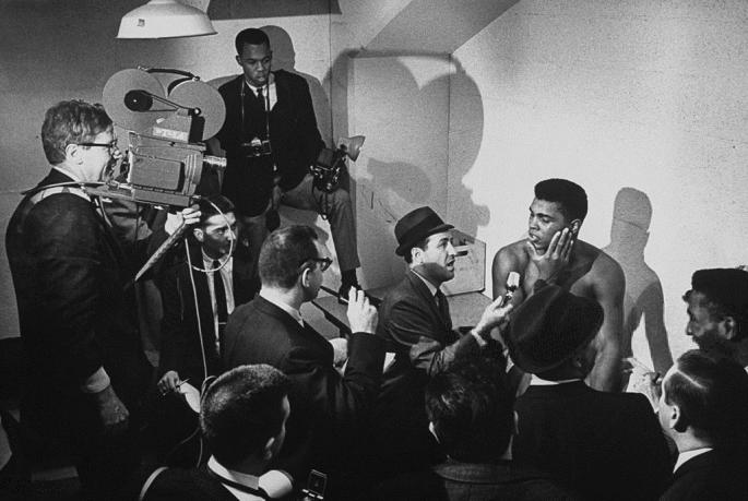 January_1963_Boxing_heavyweight_contender_Cassius_Clay_(now_Muhammad_Ali)_speaking_to_press_about_his_fight_with_opponent_Charlie_Powell._