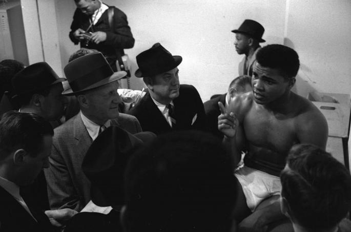 Cassius_Clay_(later_known_as_Muhammad_Ali,_1942_-_2016)_talks_with_the_press_before_a_bout_(against_Charlie_Powell)_at_Civic_Arena,_Pittsburgh,_Pennsylvania,_January_24,_1963